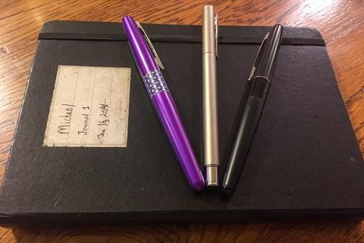 Three fountain pens on a notebook